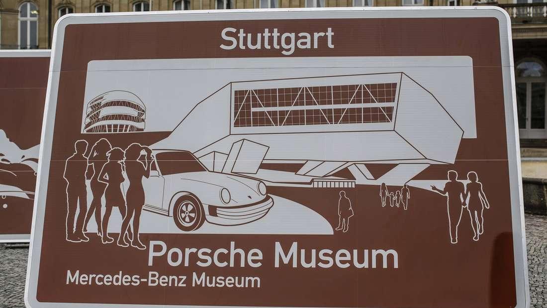Ein braunes Hinweisschild für Porsche-Museum und Mercedes-Benz-Museum in Stuttgart