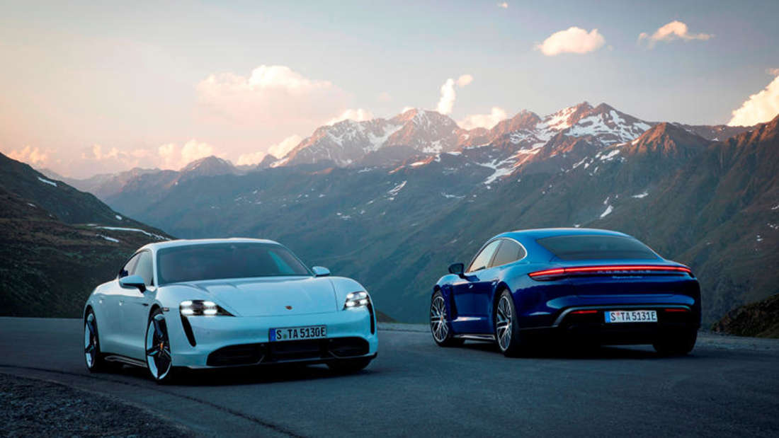 Ein weißer und ein blauer Porsche Taycan stehen nebeneinander auf einer szenischen Gebirgsstraße.
