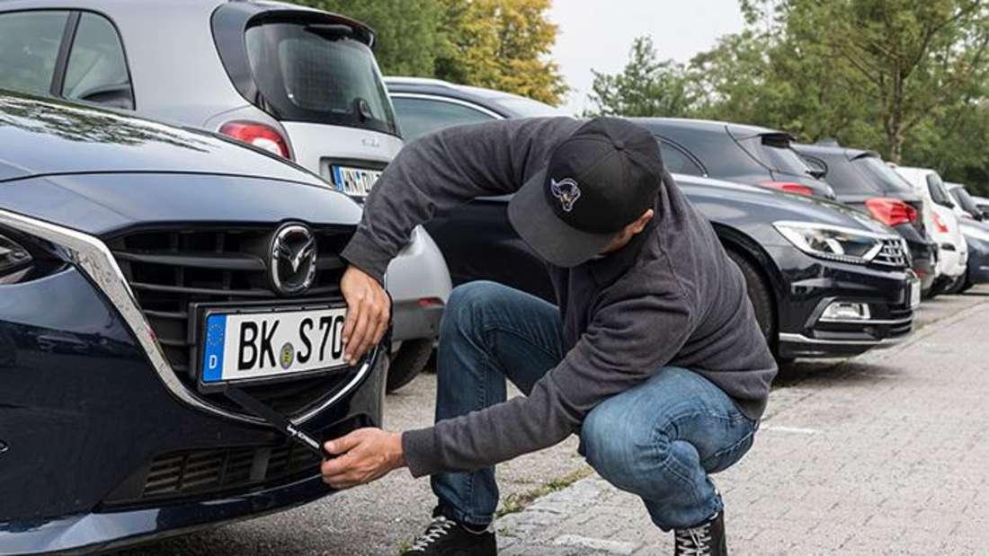 Ein Mann entfernt ein Nummernschild von einem Fahrzeug.