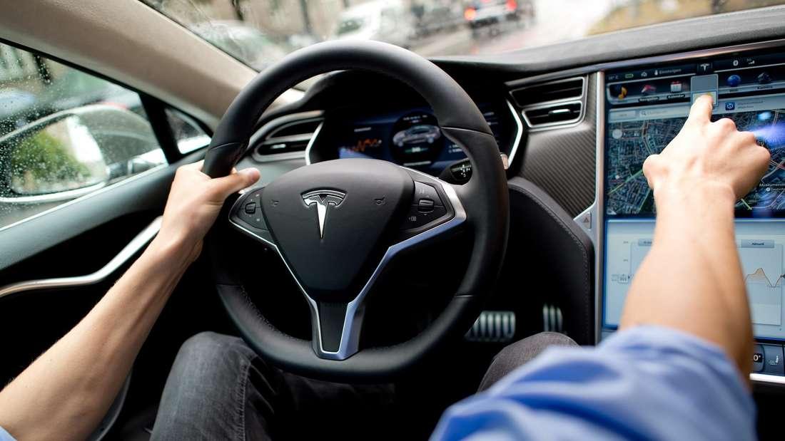Der Fahrer eines Tesla Model S bedient den Touchscreen.