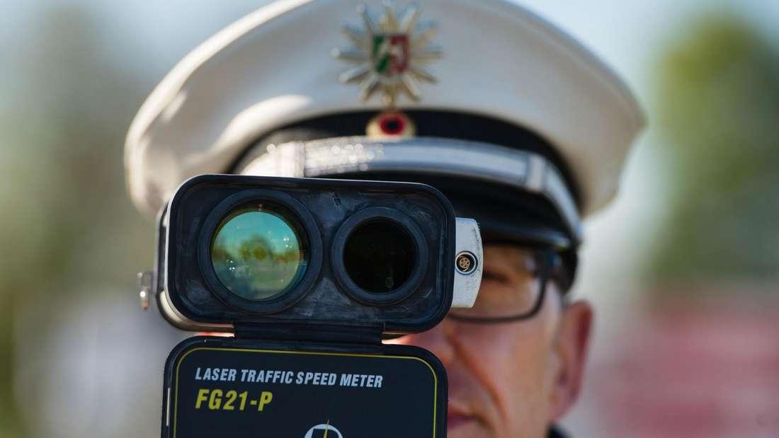 Ein Verkehrspolizist kontrolliert mit einer Laserpistole die Geschwindigkeit der vorbeifahrenden Fahrzeuge.