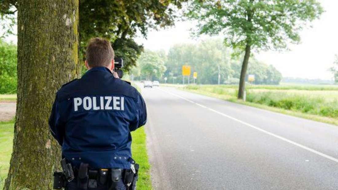Ein Polizist bei einer Geschwindigkeitsmessung am Rande einer Landstraße