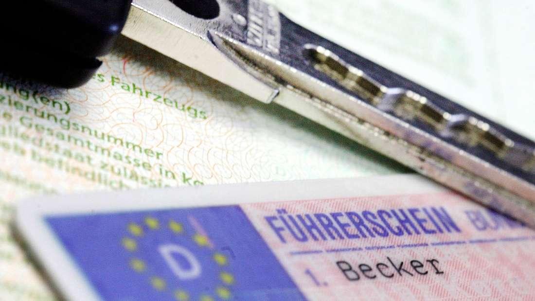 Ein Fahrzeugschlüssel und ein deutscher Führerschein im Scheckkartenformat