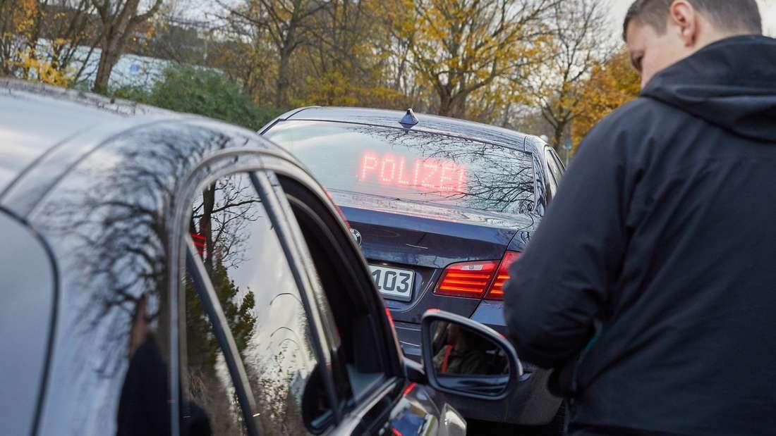 Zivile Polizeibeamte haben ein Fahrzeug angehalten und führen eine Kontrolle durch. (Symbolbild)