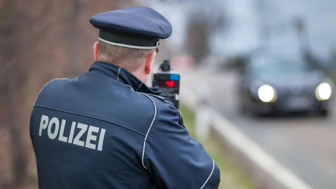 Ein Polizist misst mit einem Laser-Messgerät die Geschwindigkeit von Autofahrern. (Symbolbild)