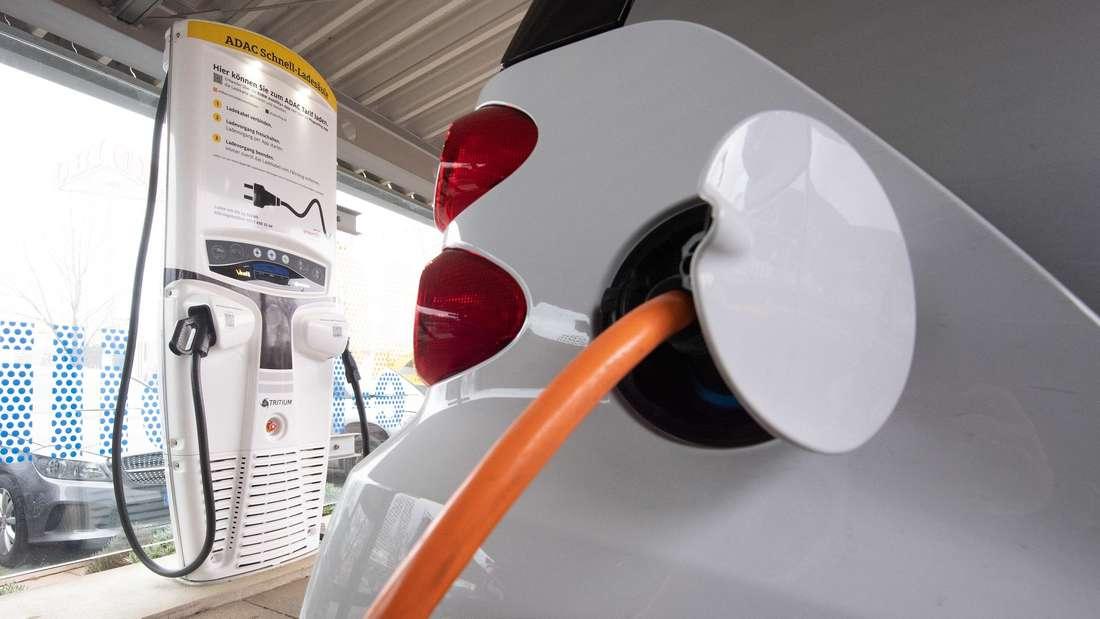 Eine Schnellladesäule und ein Elektroauto stehen an einer Geschäftsstelle des ADAC.