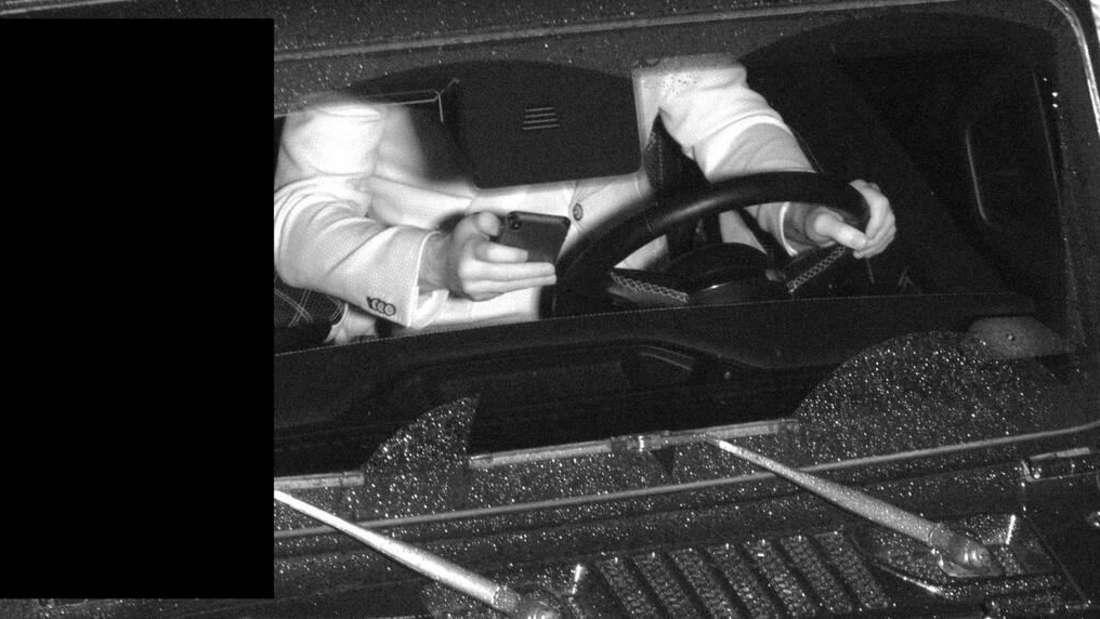 Ein Autofahrer mit Handy am Steuer, der von der niederländische Smartphone-Blitzer-Anlage aufgenommen wurde.