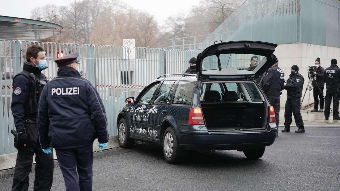 Ein dunkelgrüner VW Golf IV Variant steht vor dem Gitter-Tor des Bundeskanzleramtes.