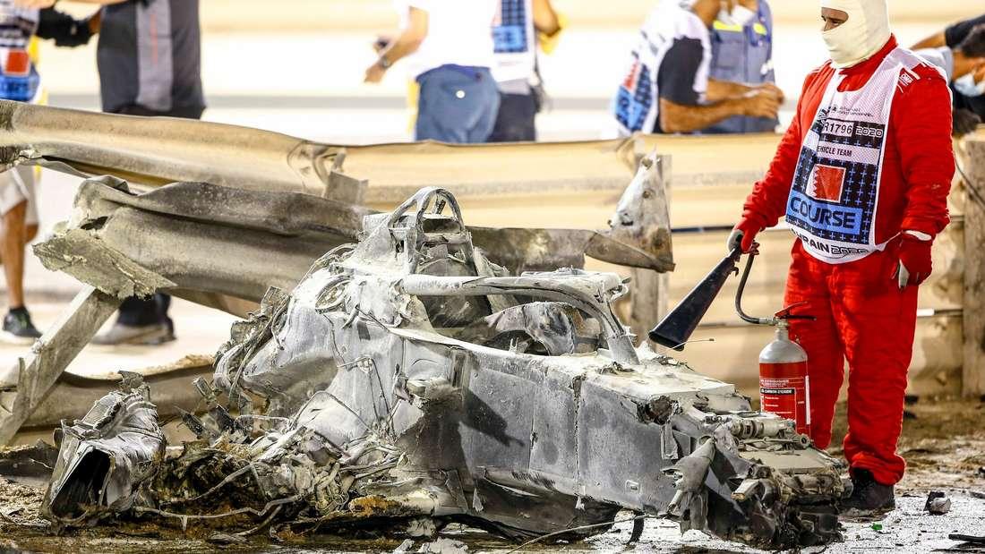 Ein Feuerwehrmann steht neben dem zusammengeschmolzenen Wrack von Romain Grosjeans Haas VF-20.