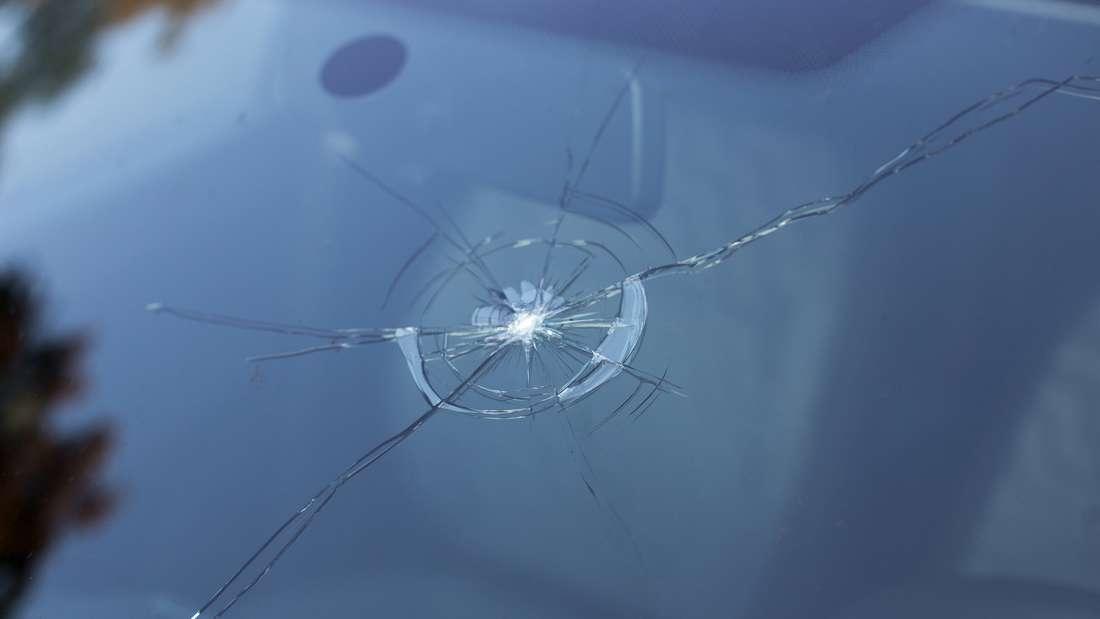 Ein durch einen Steinschlag ausgelöster Riss in der Windschutzscheibe eines Autos