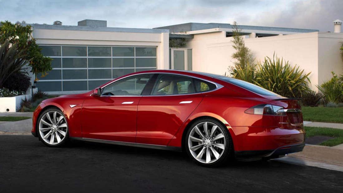 Ein rotes Tesla Model S steht vor einem Haus.