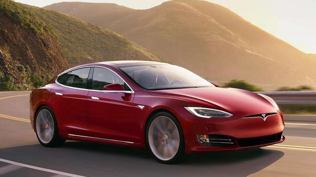 Ein rotes Tesla Model S Elektroauto fährt auf einer kurvigen Landstraße.