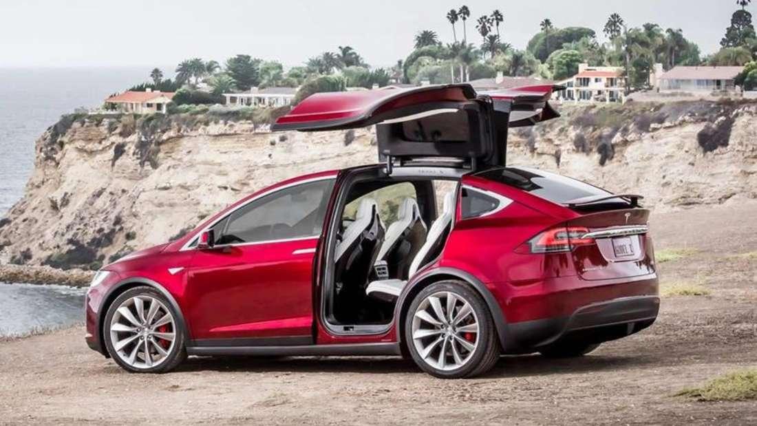 Ein Tesla Model X Elektroauto steht mit geöffneten Flügeltüren an einem Strand.