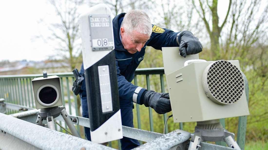 Ein Polizist hantiert an einem mobilen Messgerät zur Geschwindigkeitskontrolle.