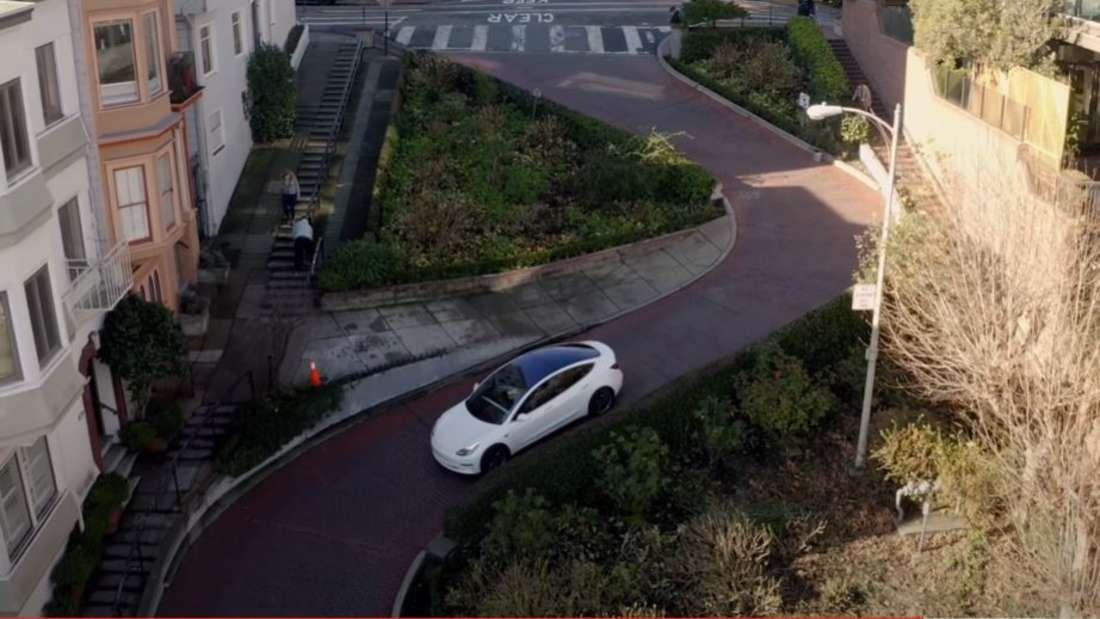 YouTuber Tesla Raj fährt mit seinem weißen Tesla Model 3 durch die Lombard Street.