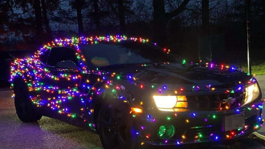 Ein schwarzer Camaro umhüllt von einer Lichterkette.