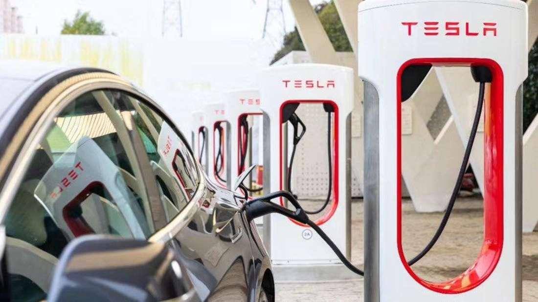Ein Elektroauto von Tesla lädt an einer Supercharger-Ladesäule Strom.