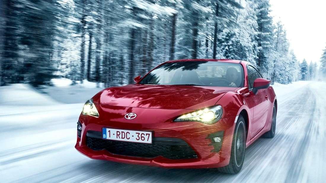 Fahraufnahme eines roten Toyota GT-86 im winterlichen Wald.