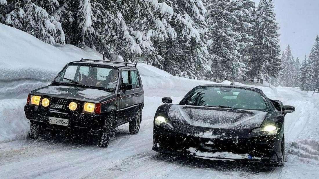 Ein Fiat Panda 4x4 (links) und ein Ferrari SF90 Stradale (rechts) duellieren sich auf einer schneebedeckten Gebirgsstraße.