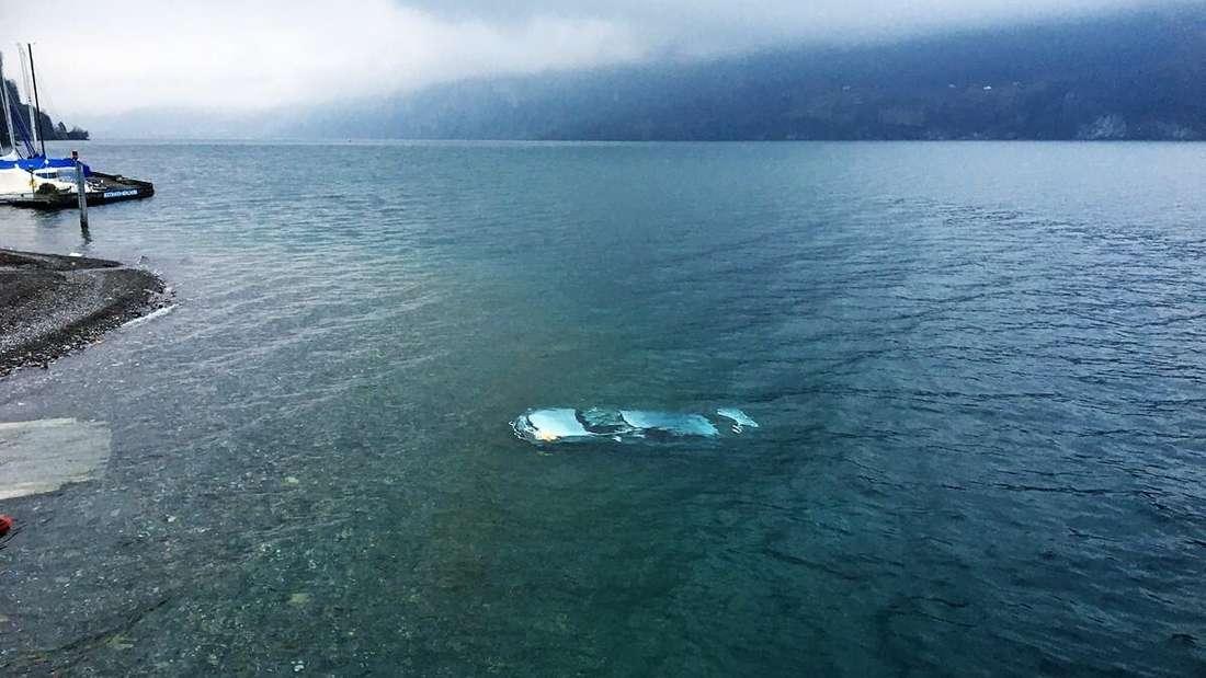 Ein Auto schwimmt unter der Wasseroberfläche eines Sees.