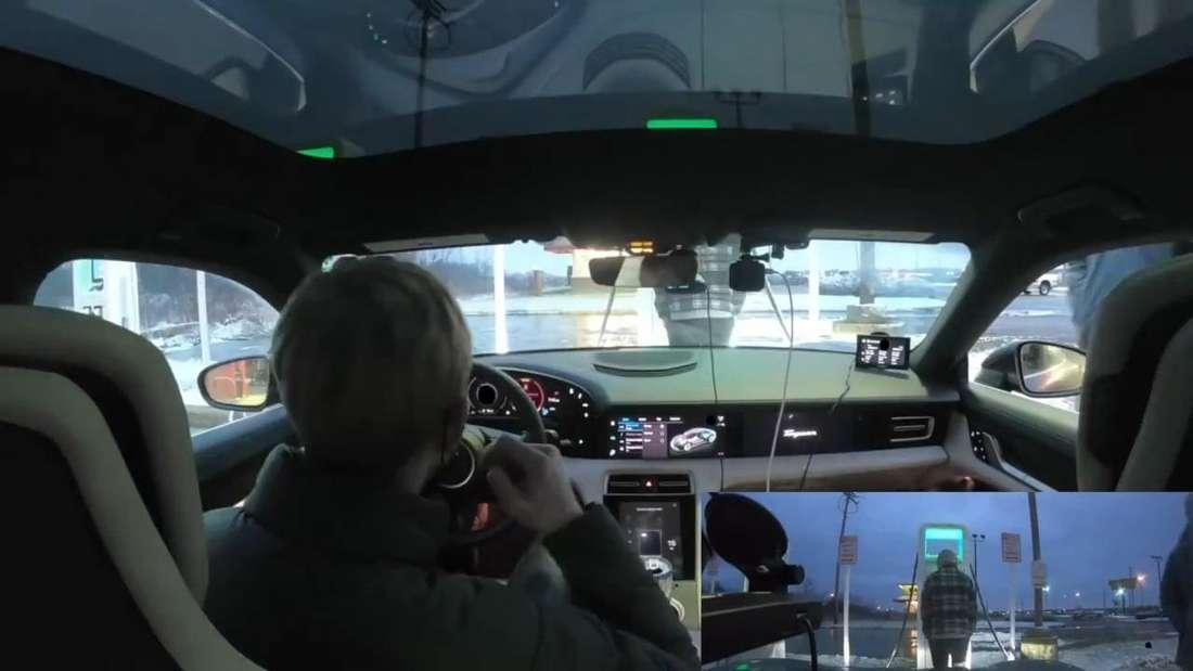 Eine Cockpit-Kamera zeigt Kyle Connor und seinen Beifahrer mit dem Porsche Taycan 4S an einer Ladestation.
