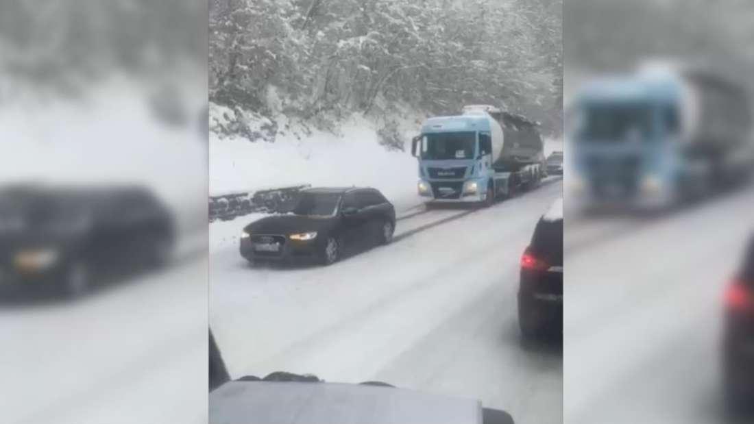Ein schwarzer Audi zieht einen Lkw im Schnee die Straße hoch.