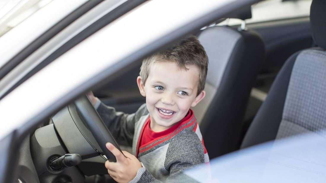 Ein kleiner Junge sitzt am Steuer eines Pkw und lacht. (Symbolbild)