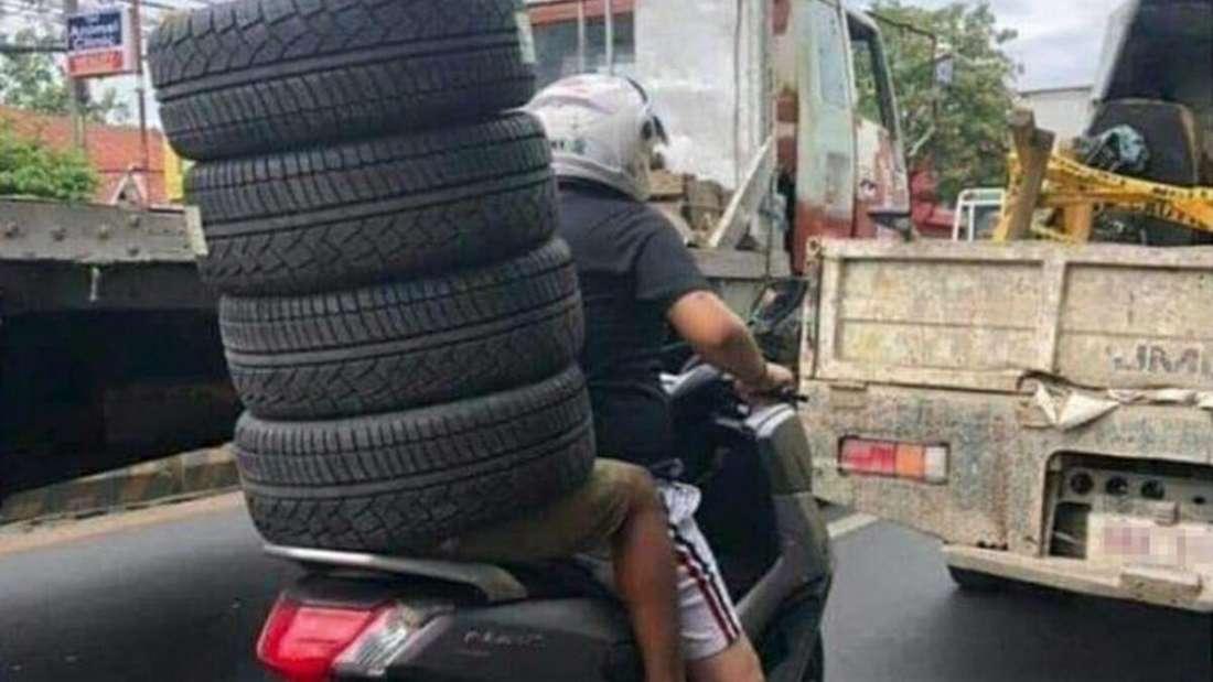 Ein Motorradfahrer und sein Beifahrer, der komplett mit Autoreifen bedeckt ist.