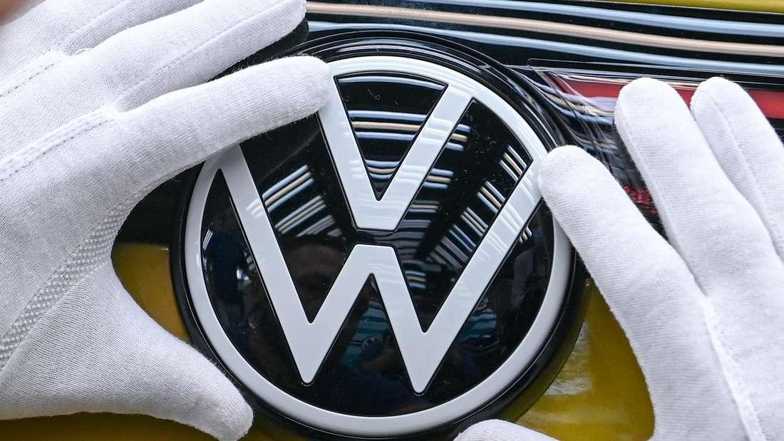 Hände umrahmen ein VW-Emblem eines VW ID.4.