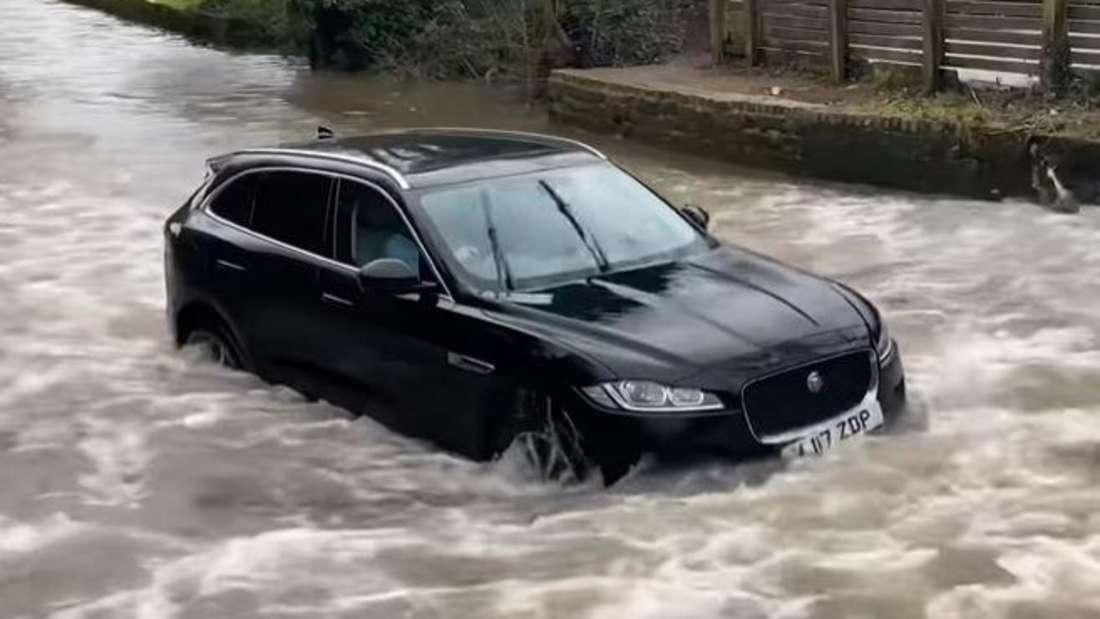 Ein Jaguar F-Pace SUV steckt im tiefen Wasser eines Bachlaufes fest.