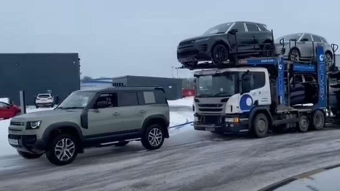 Ein Land Rover Defender 110 zieht einen Sattelschlepper über Eis und Schnee.