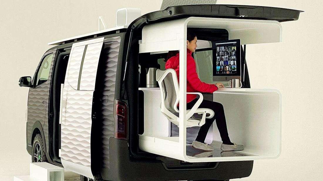 Eine Frau sitzt am Büroarbeitsplatz des Nissan Office Pod Concept und bedient einen Computer.