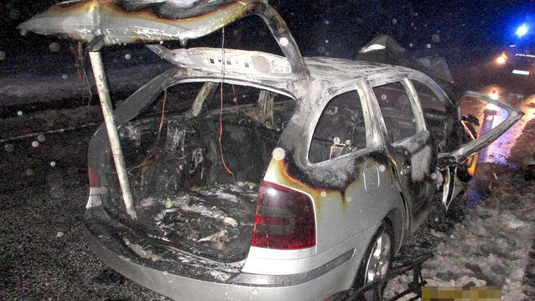 Ein völlig ausgebrannter Škoda Octavia Combi steht am Straßenrand.