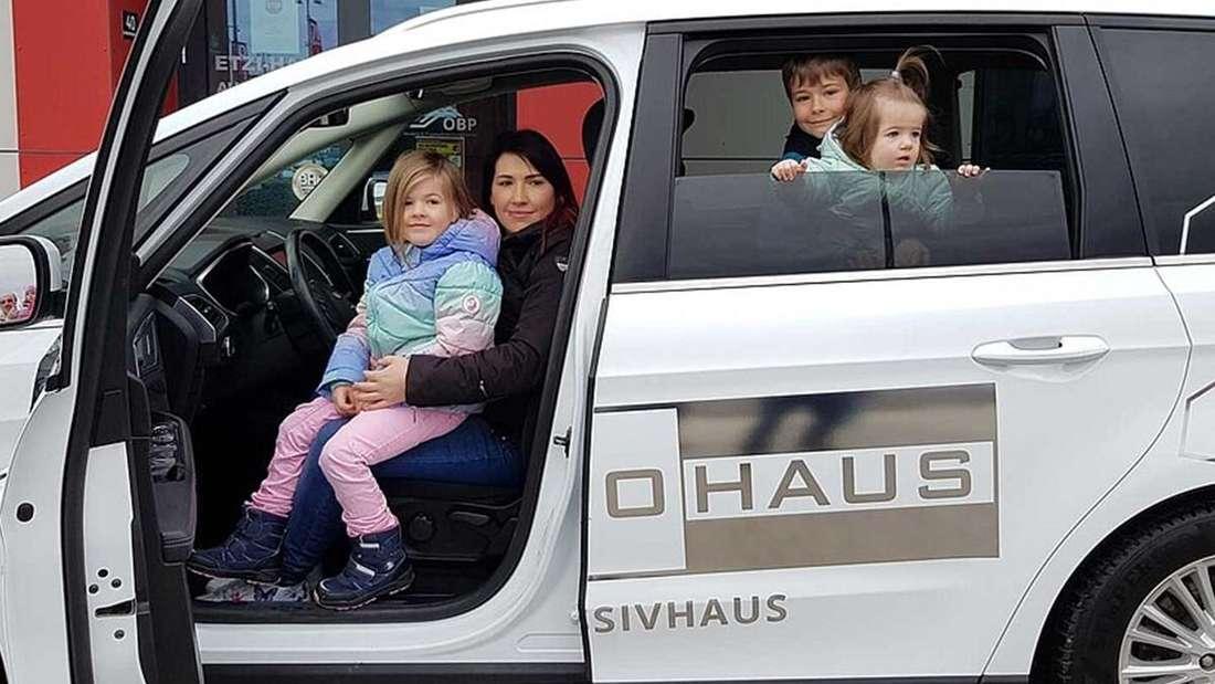 Mutter Karin mit drei Kindern im Firmenwagen von ETZI-HAUS.
