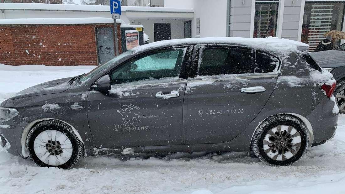 Der Fiat Tipo eines Pflegedienstes auf verschneiter Straße