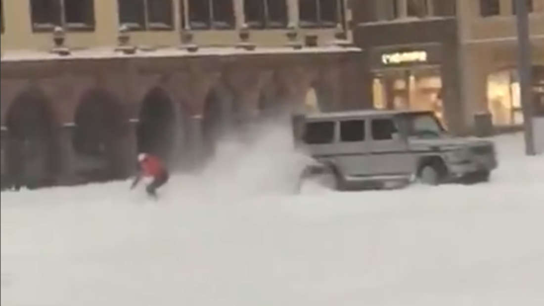 Eine Mercedes G-Klasse zieht einen Snowboarder im Schnee über den Leipziger Markt.