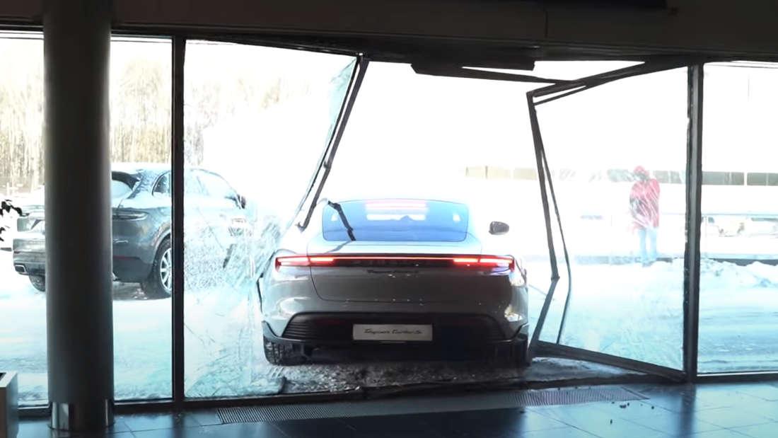 Ein Porsche Taycan Turbo S steht in der demolierten Glasfront eines Porsche-Händlers.