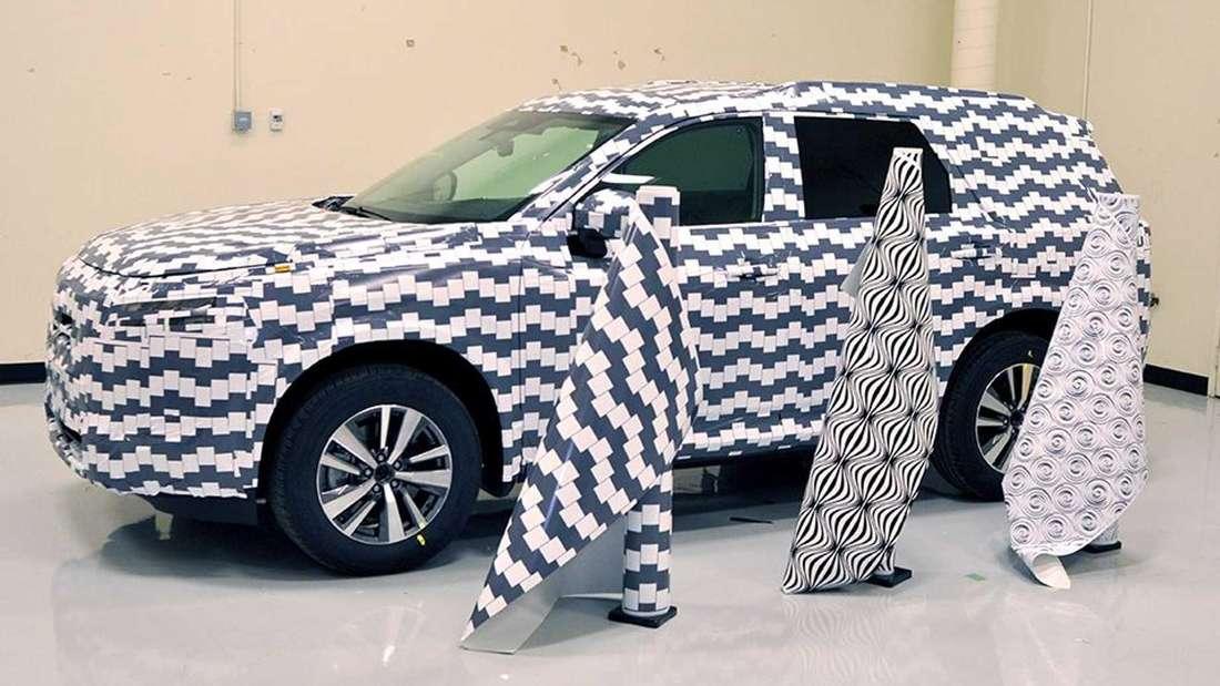 Drei Rollen mit verschieden gemusterten Tarnfolien stehen vor einem verkleideten Nissan Pathfinder SUV.
