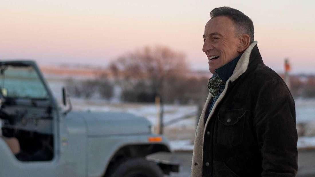 Der Sänger Bruce Springsteen steht vor einem Jeep.