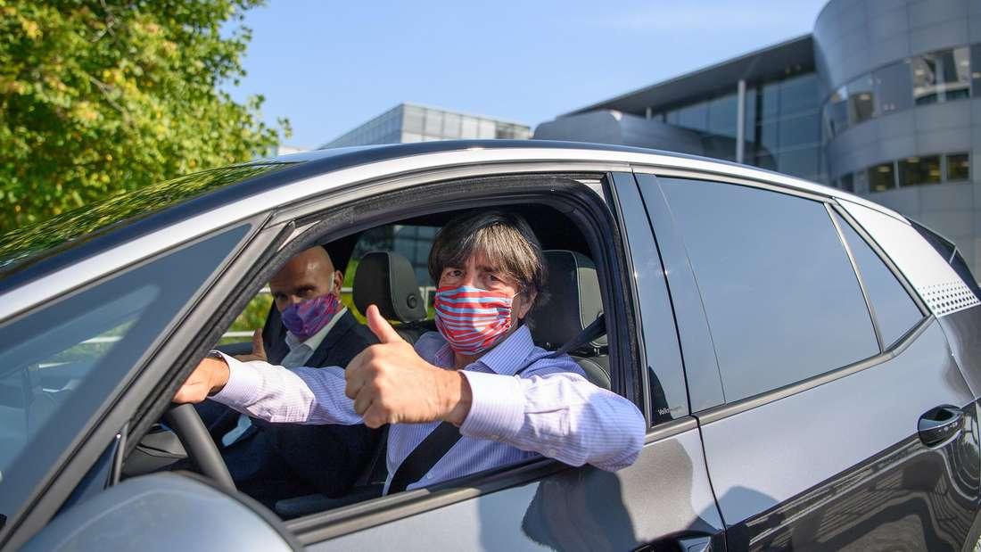 DFB-Bundestrainer Joachim Löw sitzt mit Mund-Nasen-Schutz am Steuer eines VW ID.3.