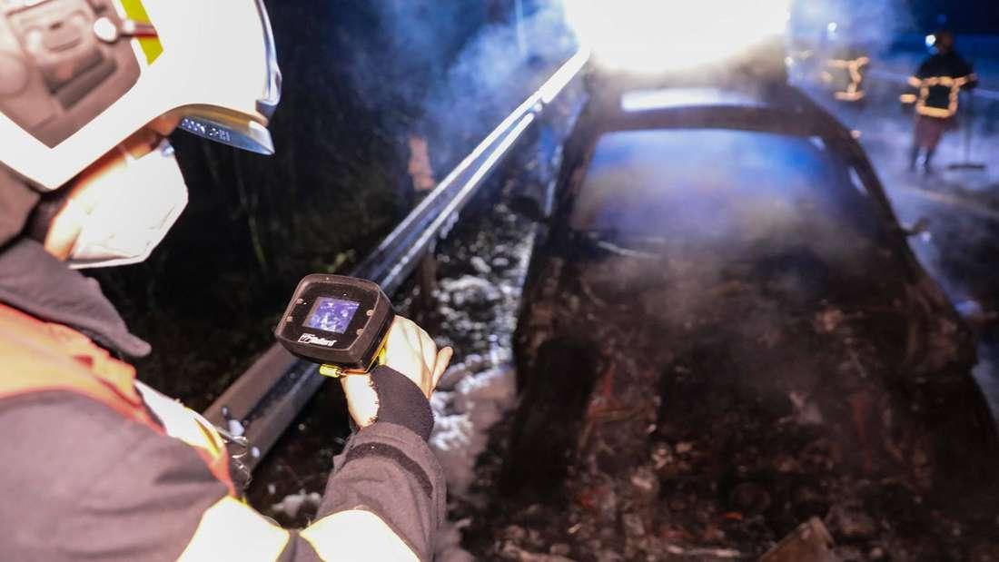 Feuerwehrleute stehen um das Wrack eines ausgebrannten Autos. (Symbolbild)