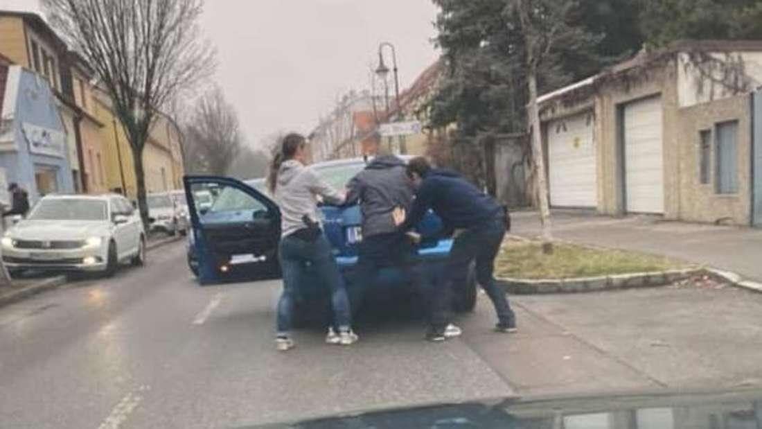 Zwei Polizeibeamte nehmen auf offener Straße einen Autofahrer fest.