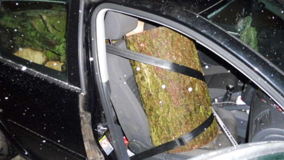 Ein Holzstamm ist auf dem Beifahrersitz angeschnallt.