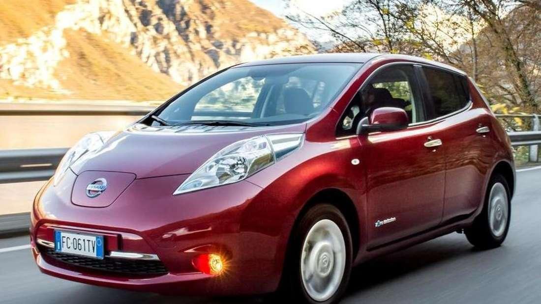 Ein Nissan Leaf fährt vor Bergpanorama über eine Landstraße.