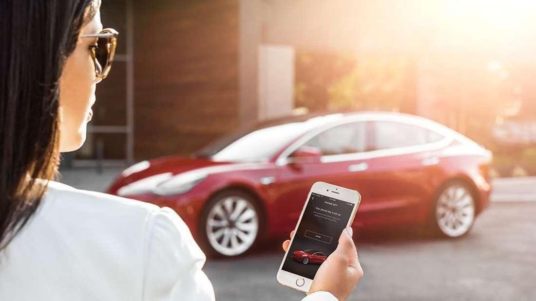 Eine Frau steht mit einem Smartphone in der Hand vor einem roten Tesla.
