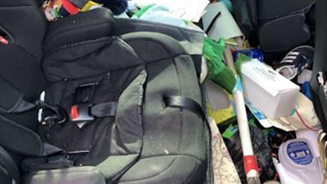 Müll, leere Reinigungsprodukte und Schuhe liegen im Inneren eines Wagens.