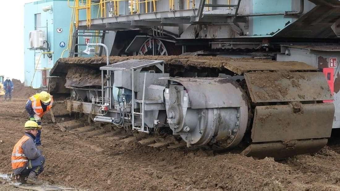 Techniker überprüfen die Ketten des riesigen Tagebau-Schaufelradbaggers.