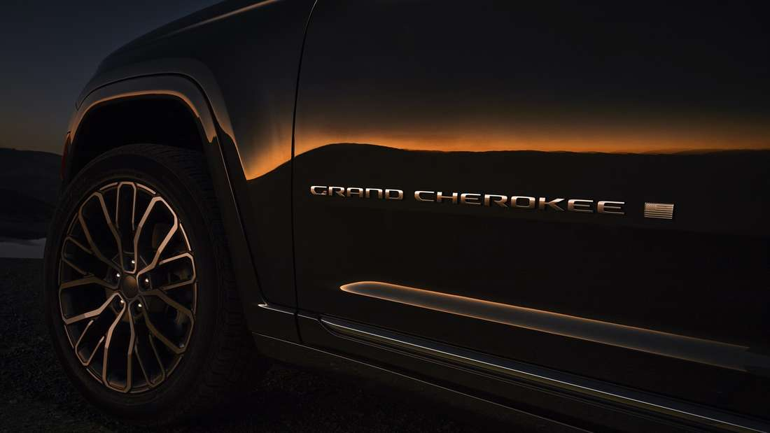 Das Badge eines Jeep Grand Cherokee glänzt in der Dämmerung.