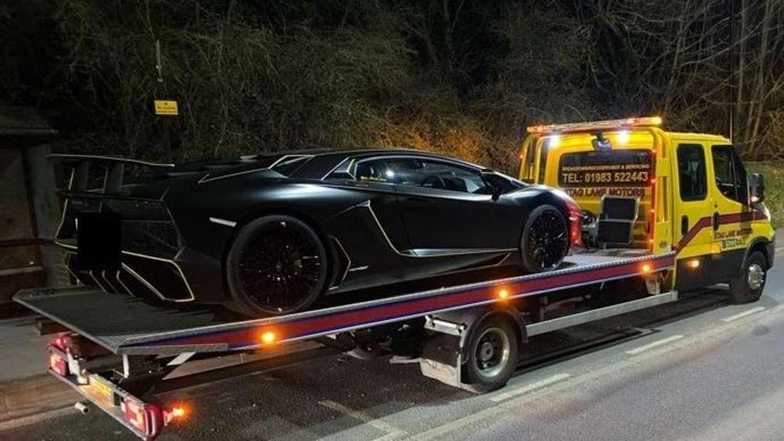 Ein schwarzer Lamborghini Aventador SV wird abgeschleppt.