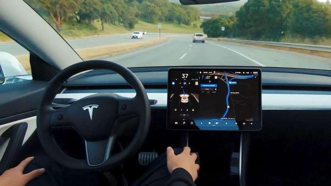 Ein Tesla-Model wird vom Autopiloten gesteuert. Der Fahrer überwacht.